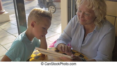 Grandmother and grandson with pad in cafe