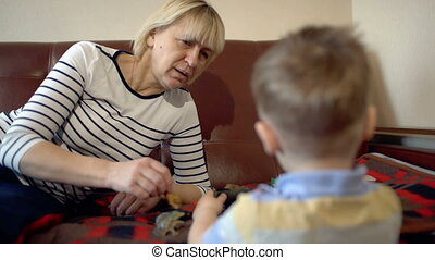 Grandmother and granson playing with toys on the sofa