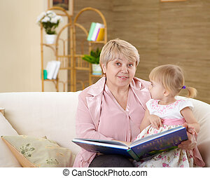 grandmother and her grandaughter - grandmother reading a...