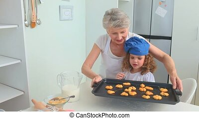 Grandmother and her granddaughter enjoying cookies that they...