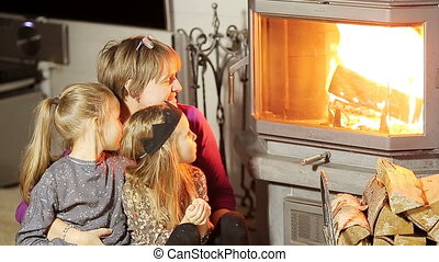 Grandmother and her two little granddaughters sitting by a fireplace in their family home on Xmas eve