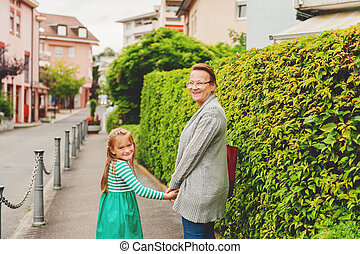 Grandmother and little girl walking outside, holding hands