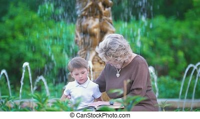 Grandmother and little grandchild reading a book near the fountain in the park