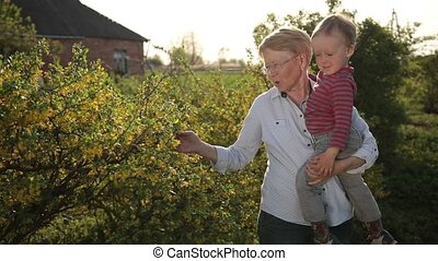Grandmother and toddler walking in spring garden