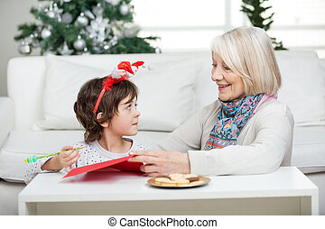 Grandmother Assisting Boy In Writing Letter To Santa Claus...