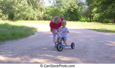 Grandmother assisting child to ride a bicycle in summer park