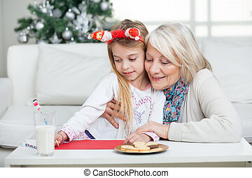 Grandmother Assisting Girl In Writing Letter To Santa Claus...
