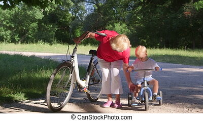 Grandmother assisting grandson to ride a bicycle