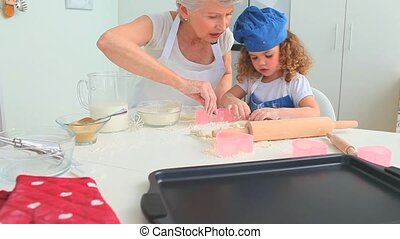 Grandmother baking cookies with her grand daughter