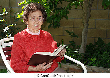 Grandmother - Bible - A kind looking elderly woman smiles as...