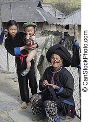 Grandmother Dao ethnic black sewing. The Dao black living in northern Vietnam. Ils are easily remarkable because women wearing embroidered black pants and their typical cap made of a large black turban over their long hair coiled