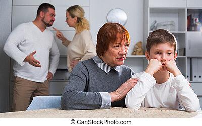 Grandmother comforting grandson while parents quarreling - ...