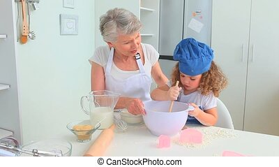 Grandmother cooking with her grand daughter