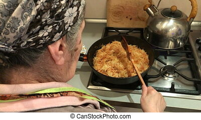 Grandmother cooks noodles in a pan