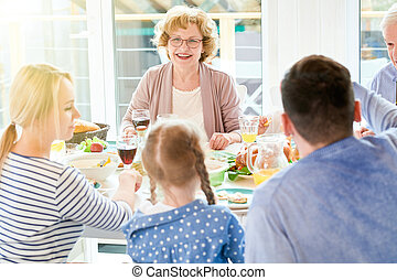 Grandmother Enjoying Family  Dinner in Sunlight