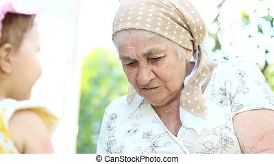Grandmother feeds her granddaughter.