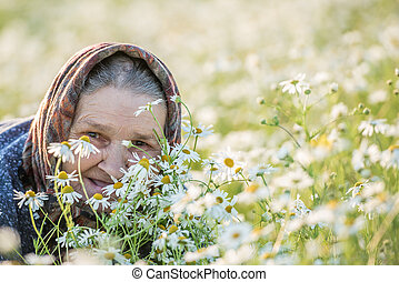 old lady in a field with daisies. Summer portrait. -...