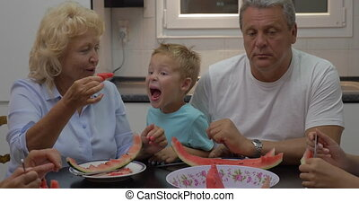 Grandmother giving watermelon to grandson