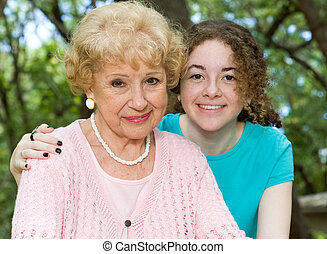 Portrait of a beautiful senior woman with her pretty teen granddaughter.