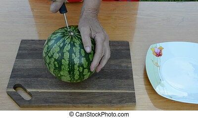 grandmother hands cut up watermelon
