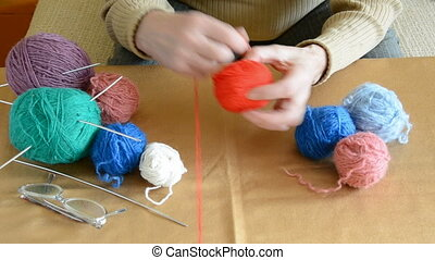 grandmother hands rolling threads in the ball