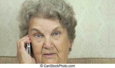 Grandmother having a call on mobile phone indoors
