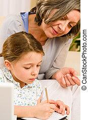 Grandmother help granddaughter doing homework