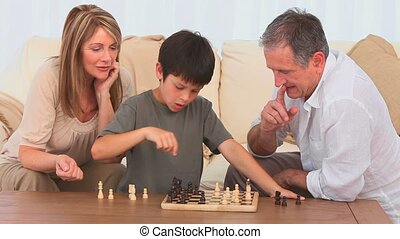 Grandmother helping her grandson to play chess