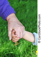 grandmother holds child's hand outdoor