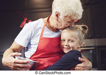 Grandmother kissing and hugging her granddaughter