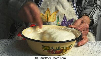 Grandmother kneads the dough