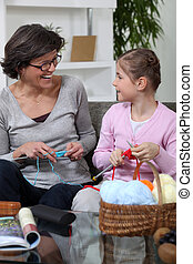 Grandmother knitting with her granddaughter