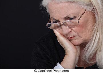 grandmother looking concerned against black background