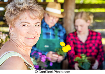 Grandmother looking into the camera. Planting flowers with ...