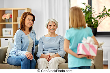 grandmother, mother and daughter with gift box