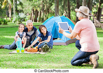Grandmother Photographing Family At Campsite