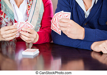 Grandmother Playing Cards With Grandson - Cropped image of...