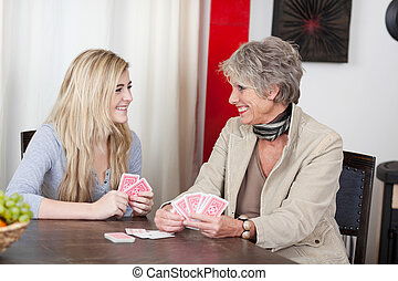 Image of a grandmother playing cards with her granddaughter and having fun.