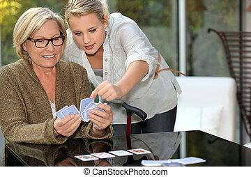 Grandmother playing cards with granddaughter