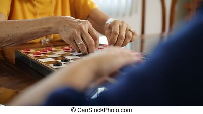 Grandmother Playing Checkers Board Game With Granddaughter...