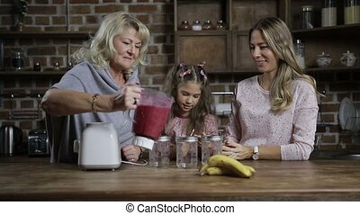Grandmother pouring berry smoothie into mason jars -...