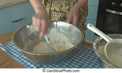 Grandmother prevents the dough in the kitchen, takes out the olive and adds it to the dishes. A woman is cooking a cookie.