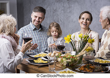 Grandmother proposing a toast with family