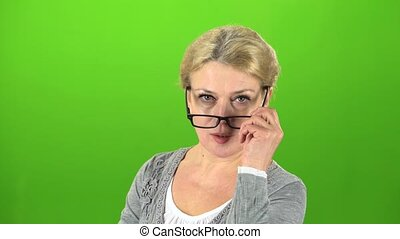 Grandmother puts on her glasses and speaks more quietly....