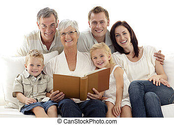 Grandmother reading a book to her children and parents in...