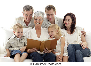 Grandmother reading a book to her family