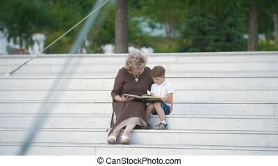 Grandmother reading a book to her grandson sitting on the stairs in the park