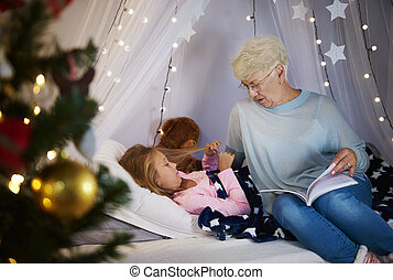 Grandmother reading a storybook to granddaughter