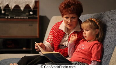 Grandmother reading a tale to her baby granddaughter.