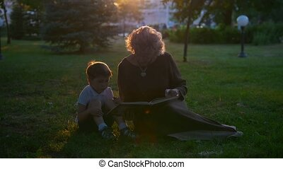 Grandmother reads a book to her grandson, sitting on the grass in the park at sunset